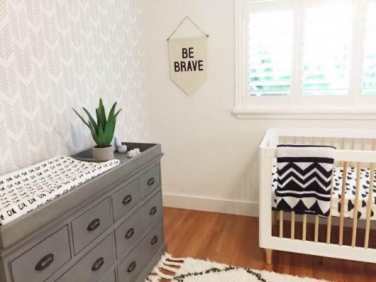 A DIY gray, white, black stenciled accent wall in a nursery using the Drifting Arrows wall pattern from Cutting Edge Stencils. http://www.cuttingedgestencils.com/drifting-arrows-stencil-pattern-diy-decor.html