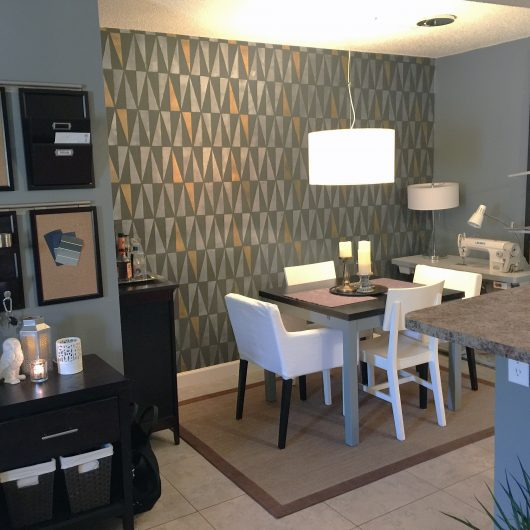 A black and gold stenciling dining room accent wall using the Geo Allover Stencil, a geometric wall pattern, from Cutting Edge Stencils. http://www.cuttingedgestencils.com/geo-wall-stencil-pattern-diy-decor.html