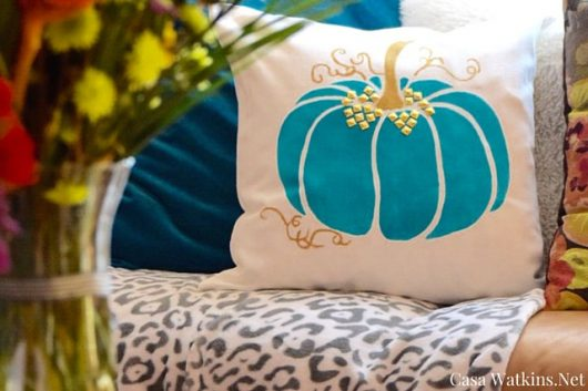 A DIY Halloween stenciled accent pillow using the Pumpkin Stencil from Cutting Edge Stencils in teal. http://www.cuttingedgestencils.com/pumpkin-stencils-halloween-throw-pillows-diy-home-decor.html