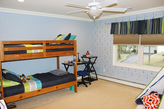 A blue and green stenciled accent wall in a boys bedroom using the Tribal Arrows Allover, a popular arrow motif wall pattern, from Cutting Edge Stencils. http://www.cuttingedgestencils.com/tribal-arrow-pattern-stencils-wall-decor.html