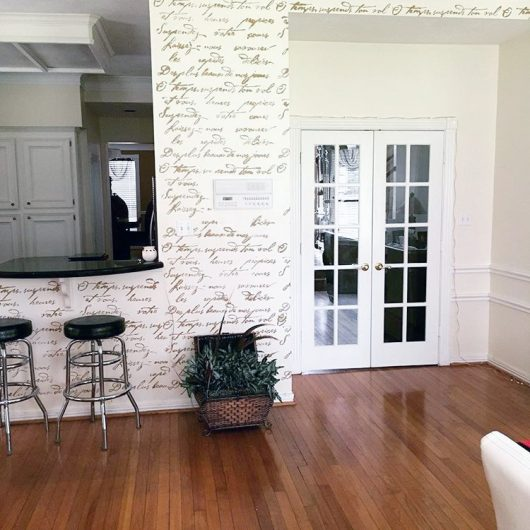 A DIY gold stenciled accent wall using the French Poem Allover Stencil from Cutting Edge Stencils. http://www.cuttingedgestencils.com/french-typography-letter-wall-stencil.html
