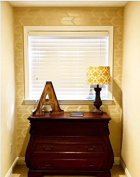A DIY golden yellow stenciled accent wall using the Drifting Arrows Allover pattern from Cutting Edge Stencils. http://www.cuttingedgestencils.com/drifting-arrows-stencil-pattern-diy-decor.html