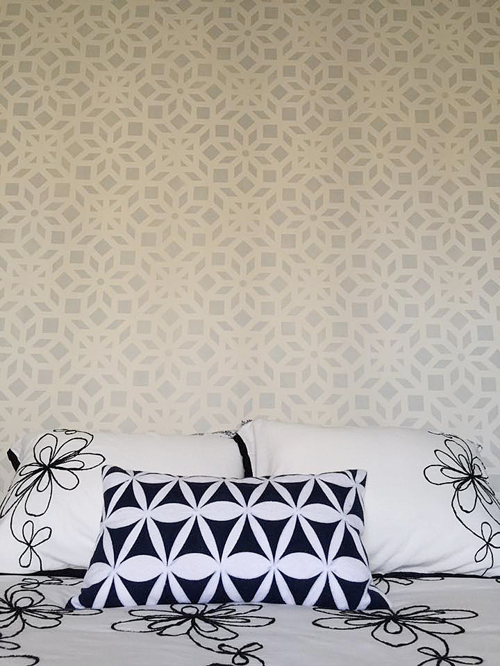 A gray and white stenciled bedroom accent wall using the Kerala Allover Stencil, an Indian inspired wallpaper pattern, from Cutting Edge Stencils. http://www.cuttingedgestencils.com/kerala-indian-stencil-geometric-pattern-stencils.html
