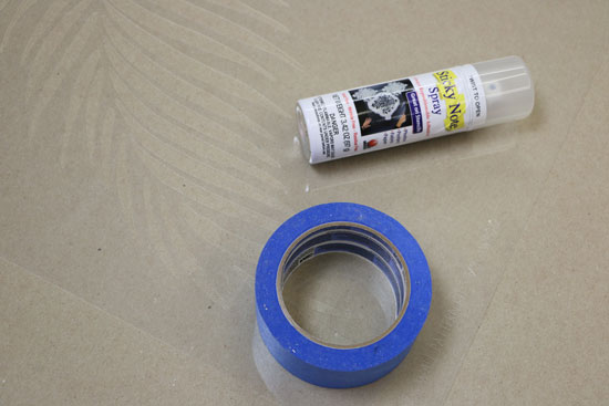 Adhesive spray and blue painters tape for stencil