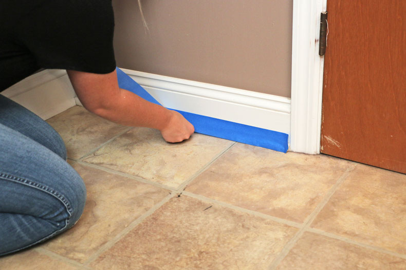 Taping perimeter of floors with blue painters tape