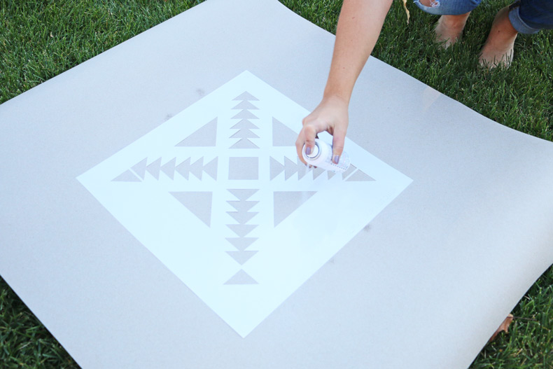 Applying spray adhesive to stencil
