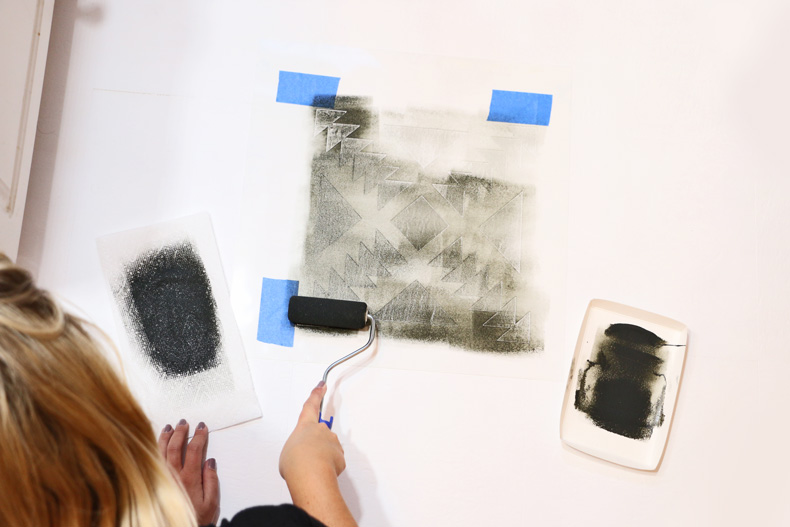 Painting over the tile stencil with foam roller