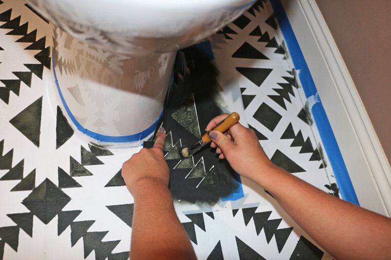 Painting around the toilet with cut stencil