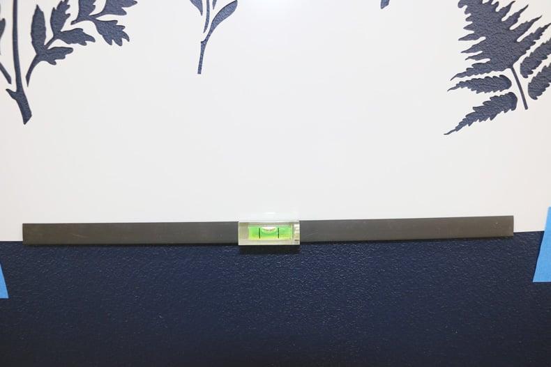 Clip on stencil level to align stencil on wall