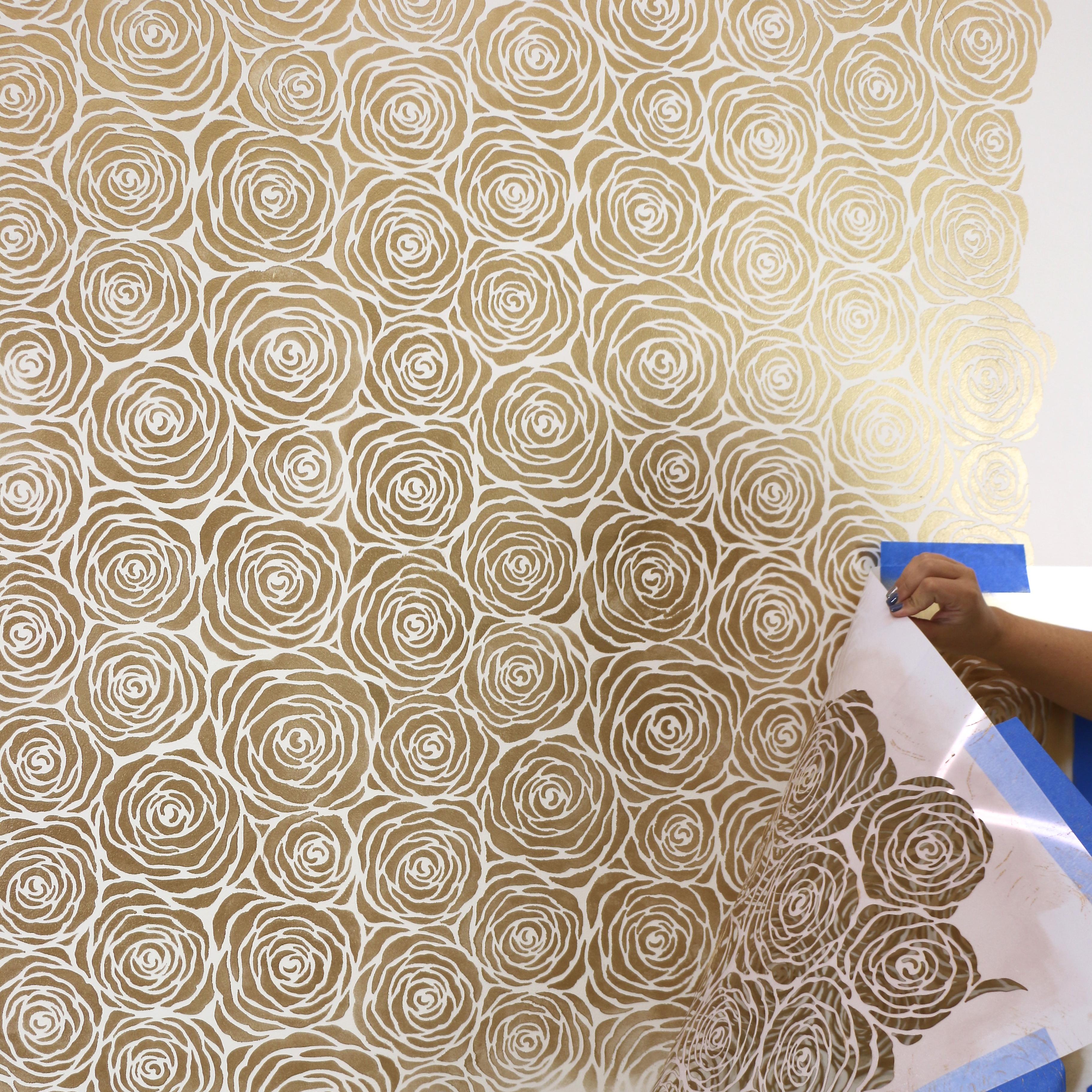 Roll metallic paint over wall stencil