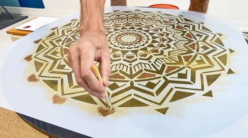 man painting over mandala stencil