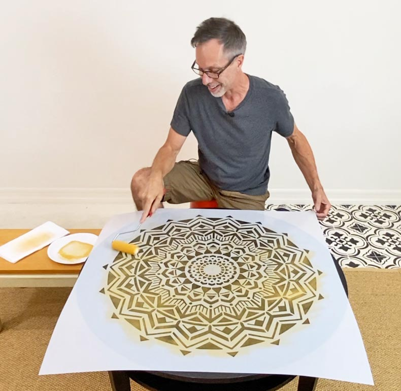 man rolling paint over stencil