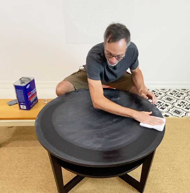man wiping down table before stenciling a mandala
