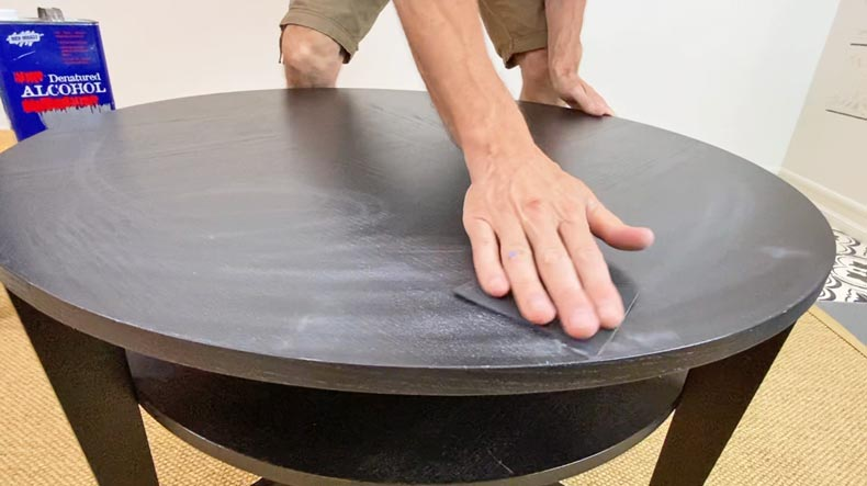 Man sanding down table before stenciling