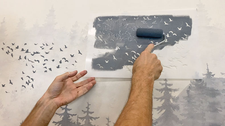 man stenciling birds in horizon of mural