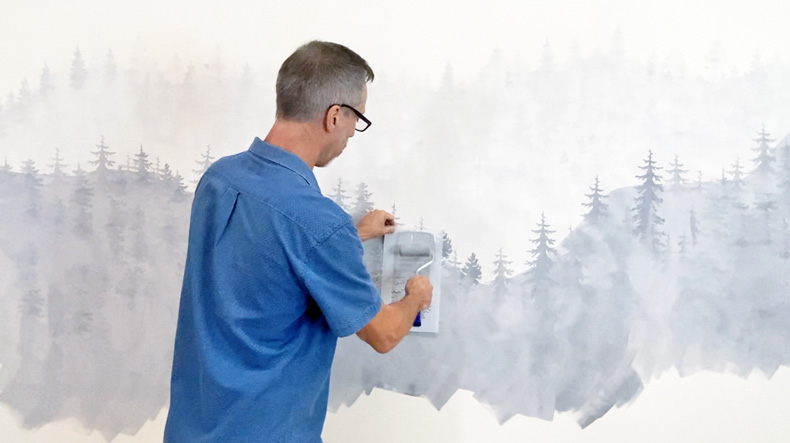 man stenciling tree in mural