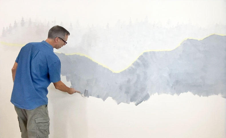 man in blue shirt stenciling wall mural