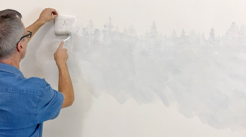 man stenciling gray pine trees