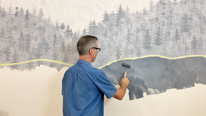 man painting wall dark gray in mountain mural