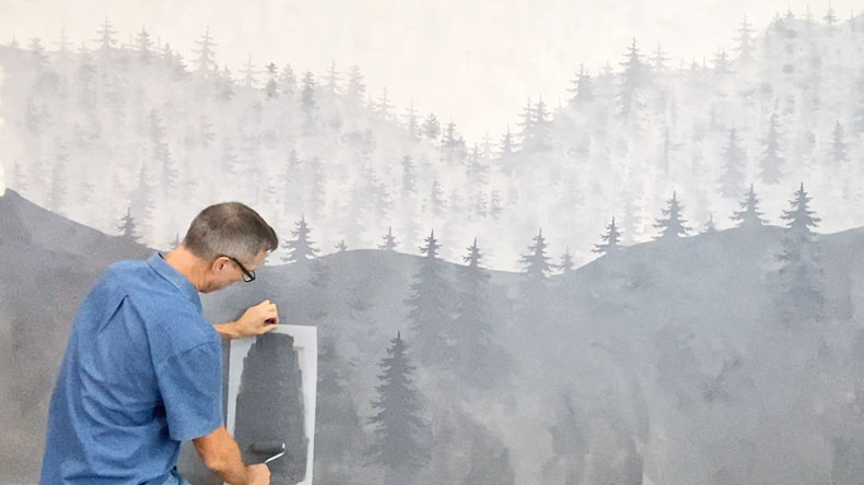man stenciling tree patterns in mural