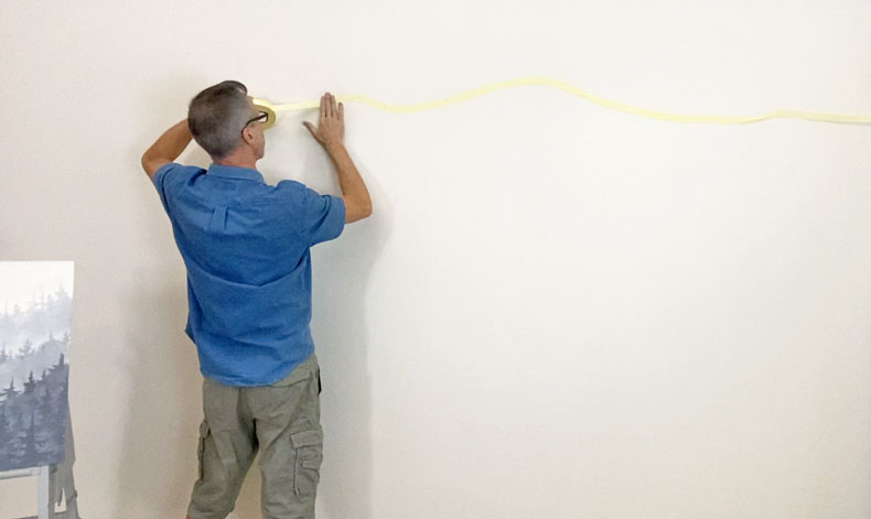 Man adding flex tape to wall before stenciling mountain mural