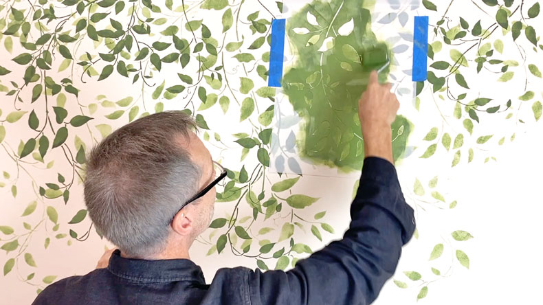man stenciling darker vine leaves