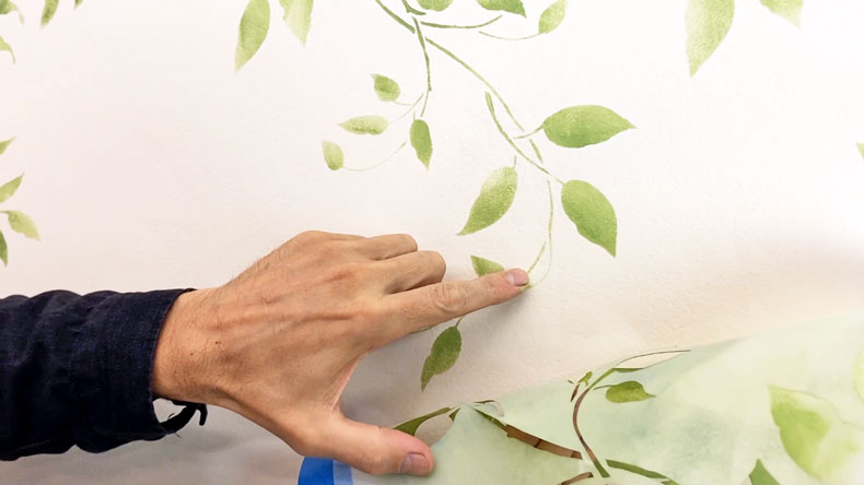 man's hand pointing at stenciled vine