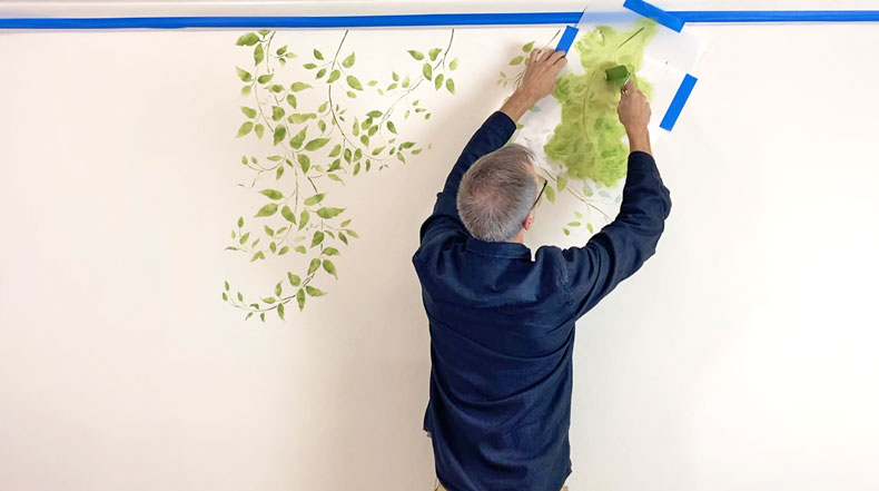 man hanging vine wall stencil on accent wall