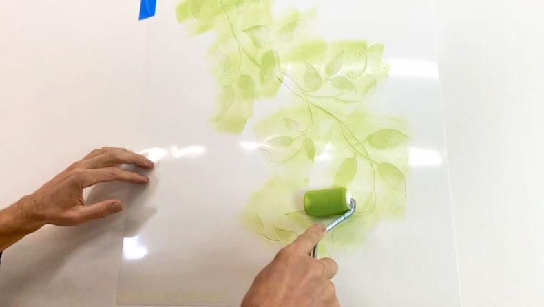 man stenciling green paint over vine stencil