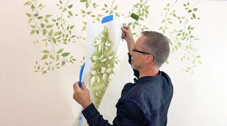 man pulling vine stencil off wall