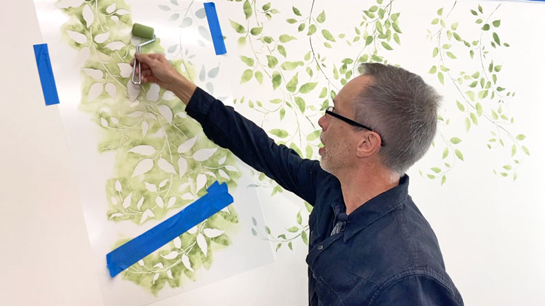 man stenciling vine stencil green