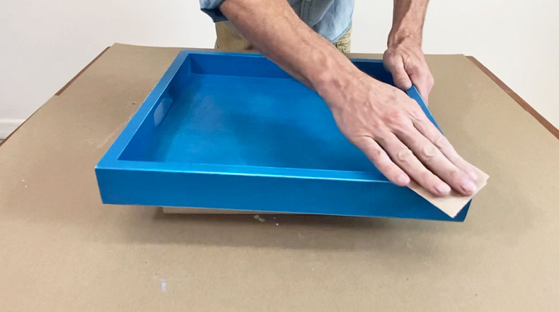 man sanding down blue serving tray