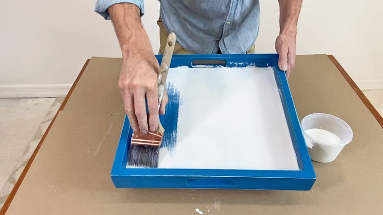 man painting blue tray with white paint