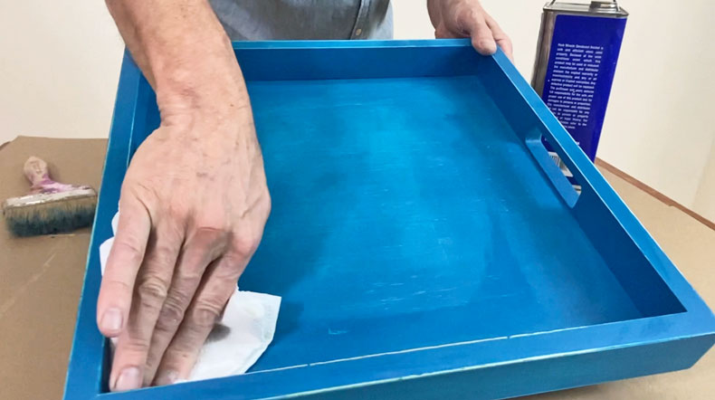 man wiping down blue serving tray with paper towel